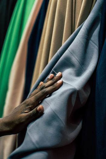 Cropped hand of man touching fabric at shop
