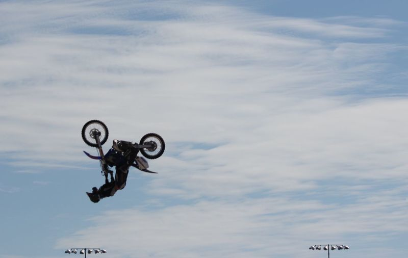 Man performing extreme stunt with motorcycle in mid-air