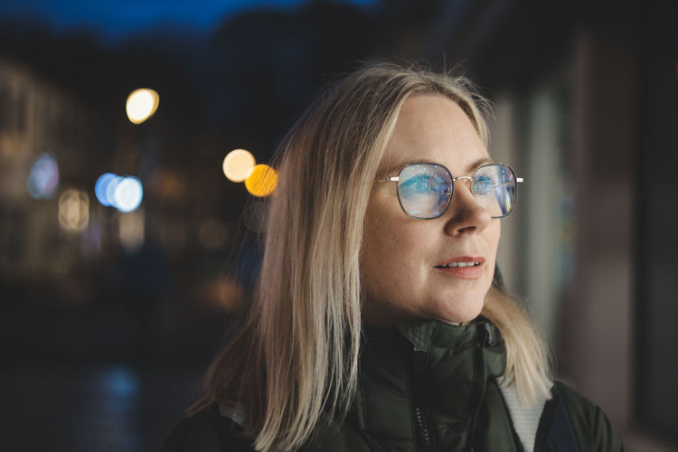 Woman with glasses in front of store window