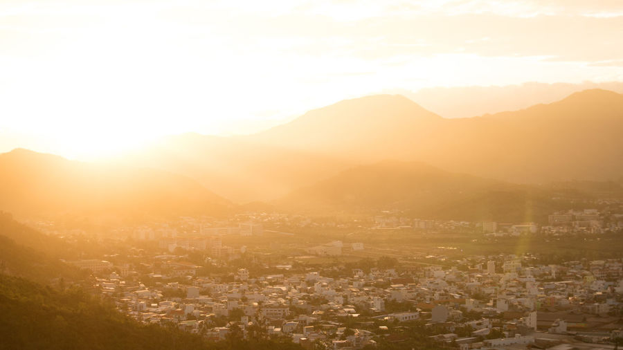 Nha Trang cityview on sunset Aerial View Architecture Bright Building Building Exterior Built Structure City Cityscape Cloud - Sky Crowded Environment Fog High Angle View Landscape Lens Flare Mountain Nature Outdoors Scenics - Nature Sky Sun Sunlight