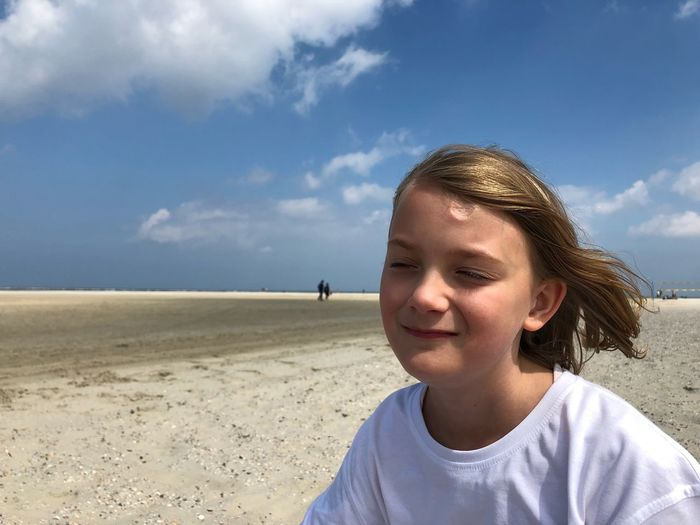 Close-up of girl with eyes closed at beach against sky