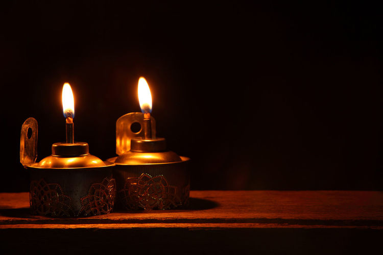Close-Up Of Oil Lamps On Wooden Table Against Black Background