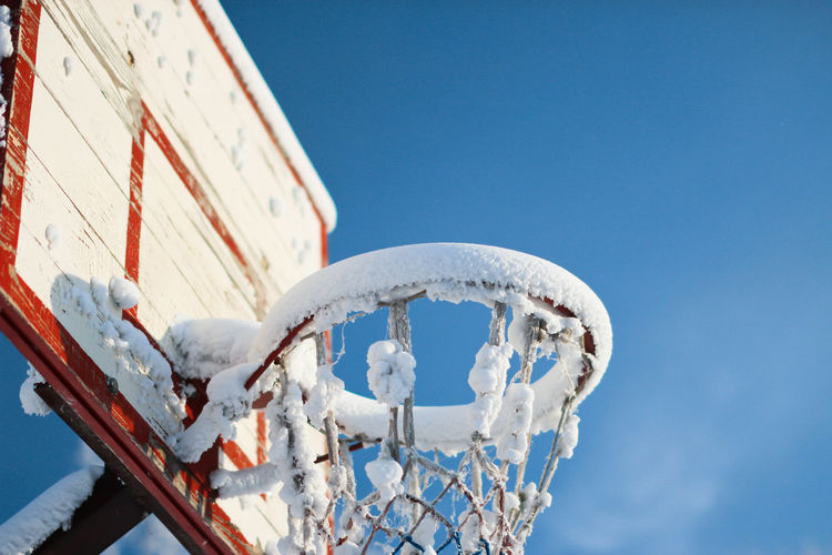 Low angle view of frozen basketball hoop against blue sky during winter