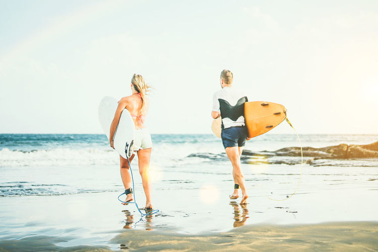 Rear View Of Friends With Surfboards Walking Towards Sea On Shore At Beach Against Sky