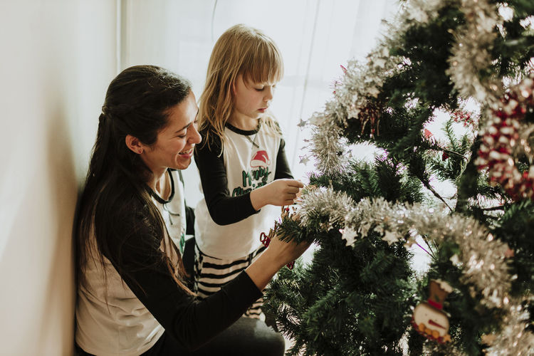 Women standing by christmas tree