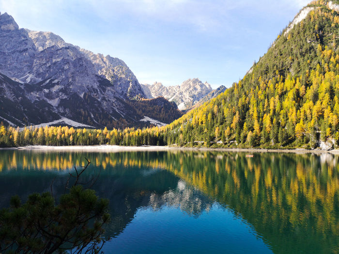 Natural landscape of braies lake with green trees, lake with reflection and mountain with snow