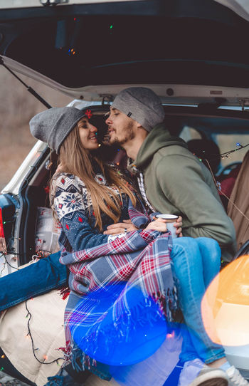 Smiling couple embracing while sitting in car trunk