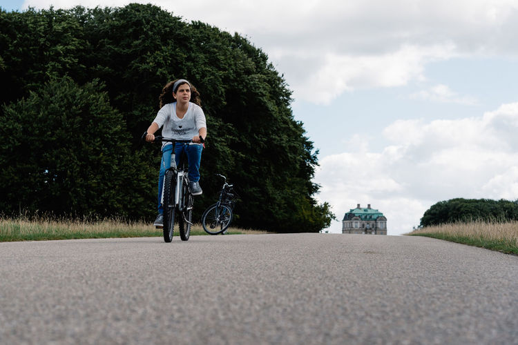 Young woman riding a bicycle in a country road in a park Adult Adults Only Casual Clothing Day Front View Full Length Leisure Activity Lifestyles One Person Outdoors People Real People Road Sky Transportation Tree Young Adult Young Women