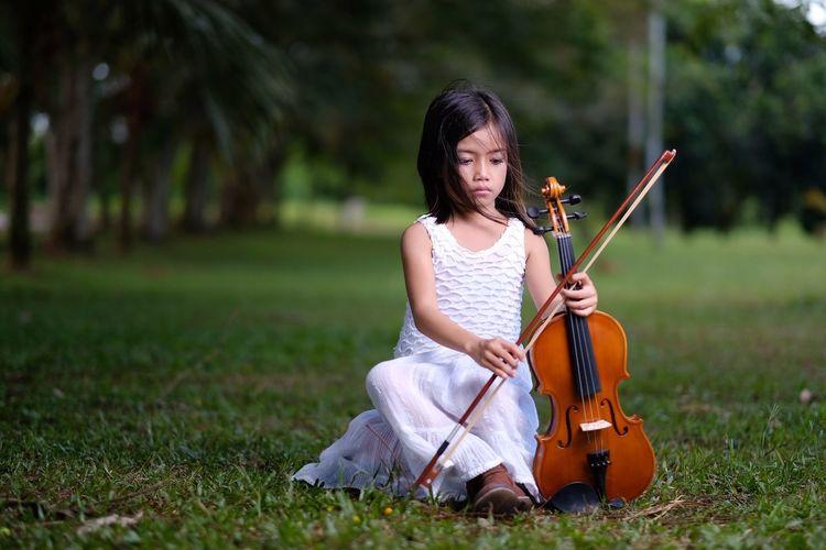 Girl playing violin on field