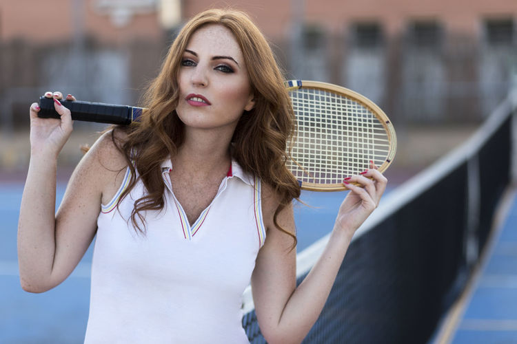Portrait Of Woman Holding Badminton Racket While Standing Against Fence