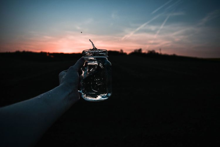 Person holding glass against sky during sunset