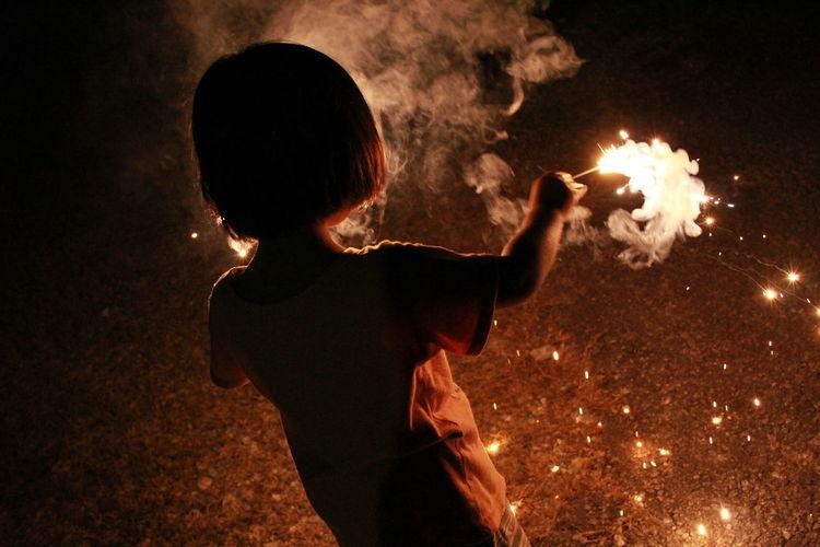 Rear view of girl burning sparkler