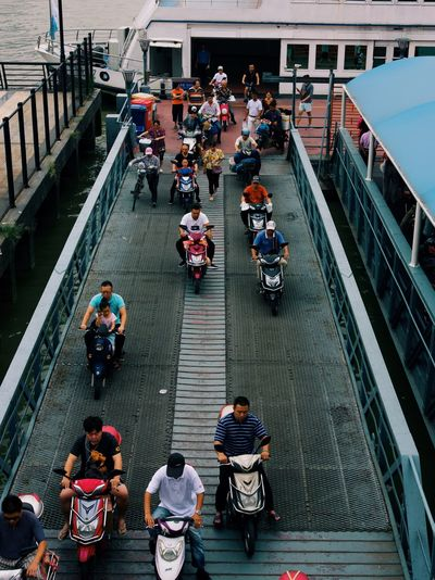 High angle view of people on motorcycles at pier