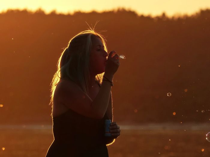 Side view of woman blowing bubbles with wand during sunset