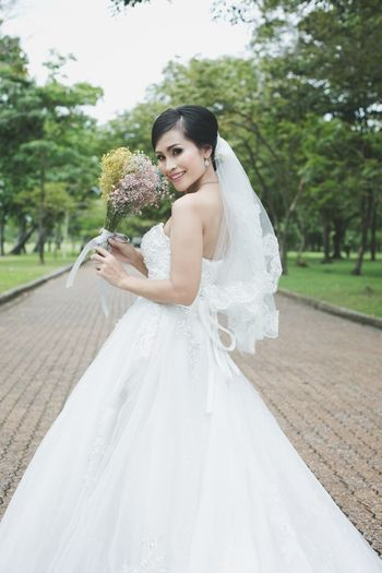 Portrait of smiling bride holding bouquet on footpath at park
