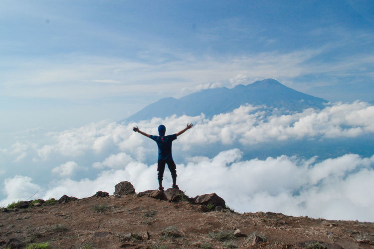 Sky Cloud - Sky Human Arm One Person Mountain Leisure Activity Lifestyles Scenics - Nature Standing Real People Beauty In Nature Limb Rock Rear View Rock - Object Arms Raised Holiday Solid Tranquil Scene Full Length Arms Outstretched Freedom Outdoors