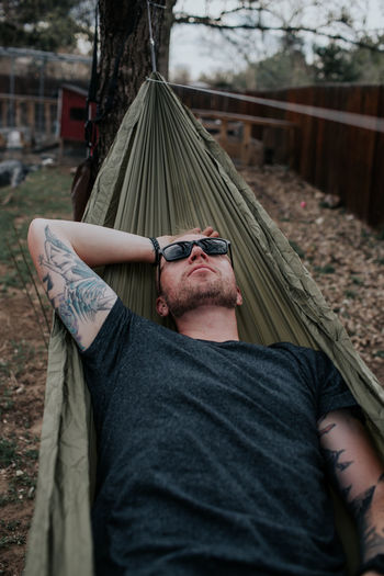 Midsection of man wearing sunglasses relaxing on tree