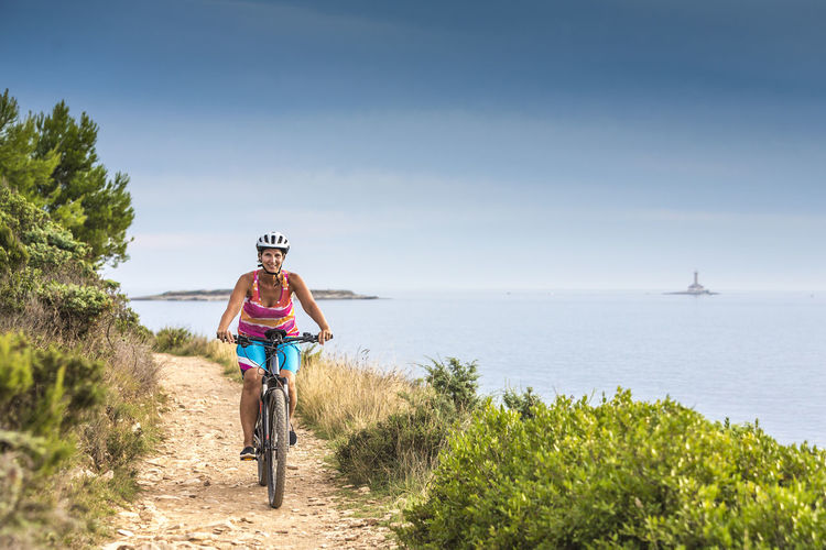 Portrait Of Woman Riding Bicycle At Beach Against Sky