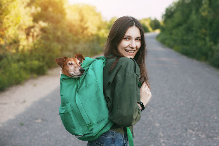 A smiling girl is holding a green backpack on her shoulder, from which a cute dog