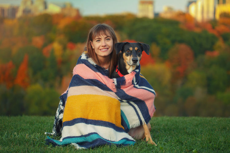 Portrait of woman with dog wrapped in shawl sitting at park