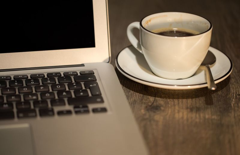 Close-Up Of Coffee Cup By Laptop On Table