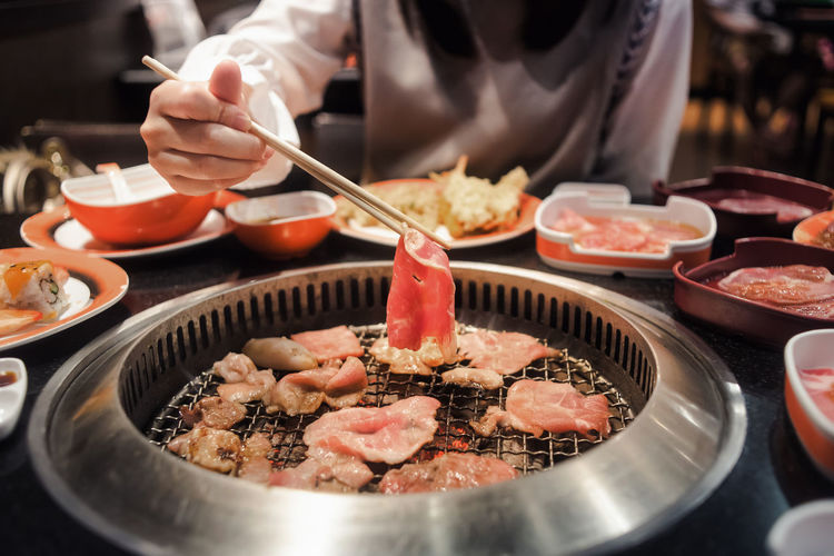 Raw beef and pork slice on grille for barbecue or Japanese style yakiniku Bowl Chopsticks Close-up Day Food Food And Drink Freshness Healthy Eating Holding Human Hand Indoors  Meat Midsection One Person Plate Ready-to-eat Real People Table