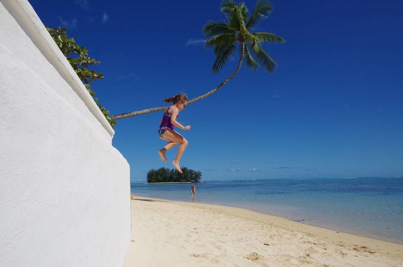 Full length of girl jumping at beach against blue sky
