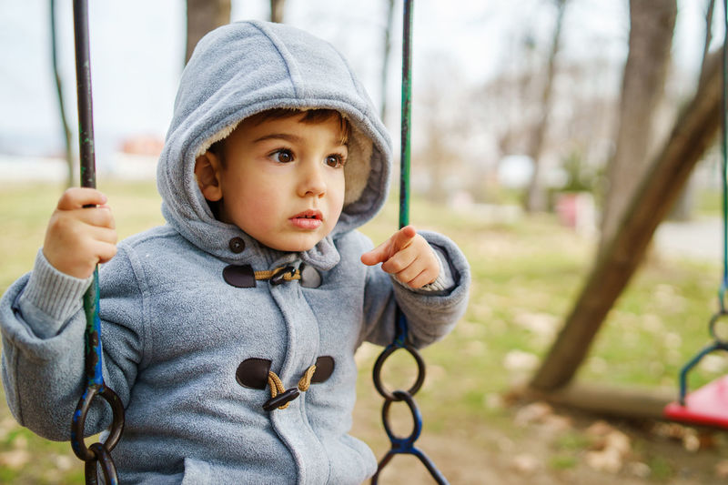 Portrait of boy holding camera at playground