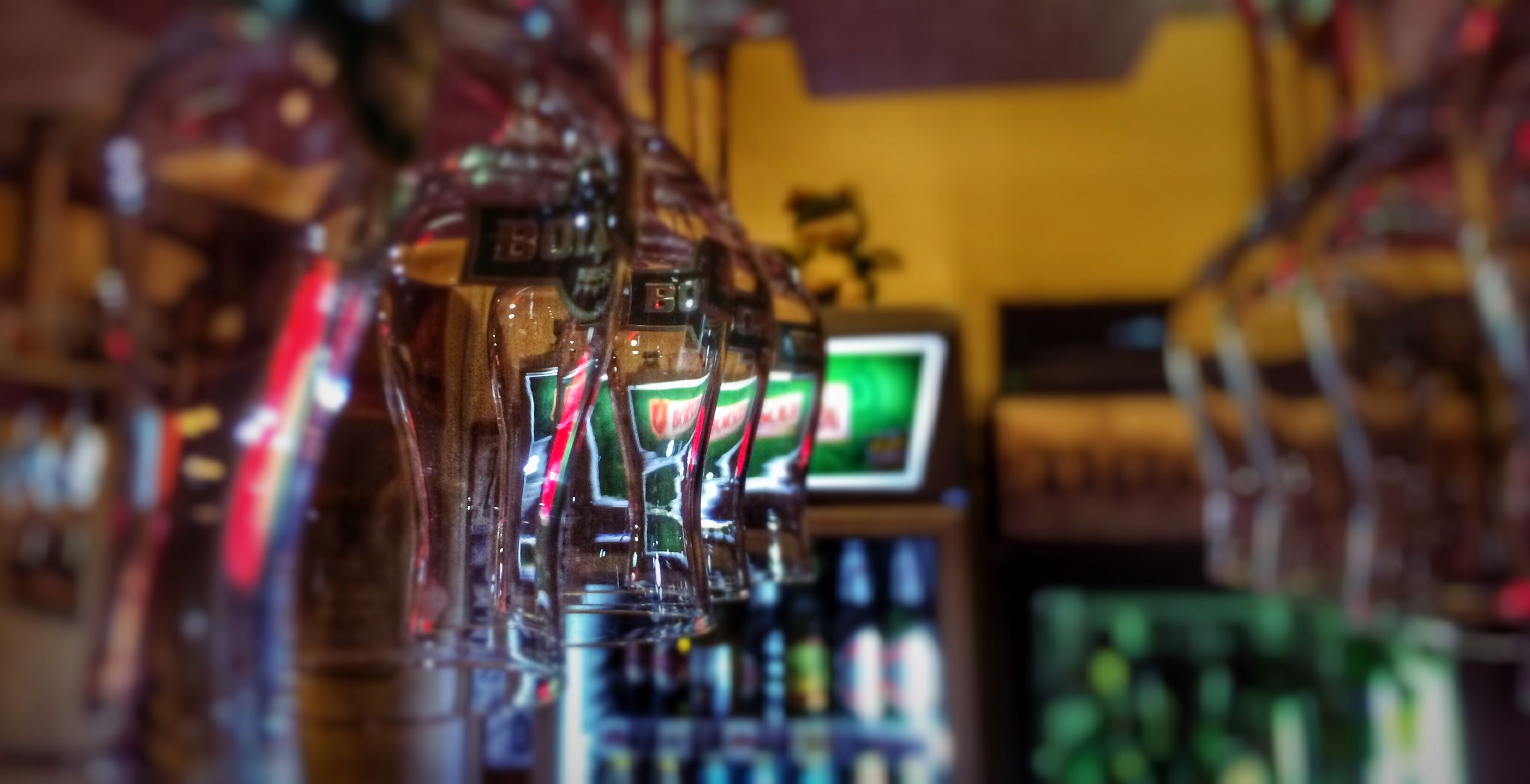 indoors, illuminated, selective focus, focus on foreground, table, multi colored, still life, variation, retail, glass - material, store, large group of objects, close-up, choice, incidental people, arrangement, night, reflection, no people, in a row