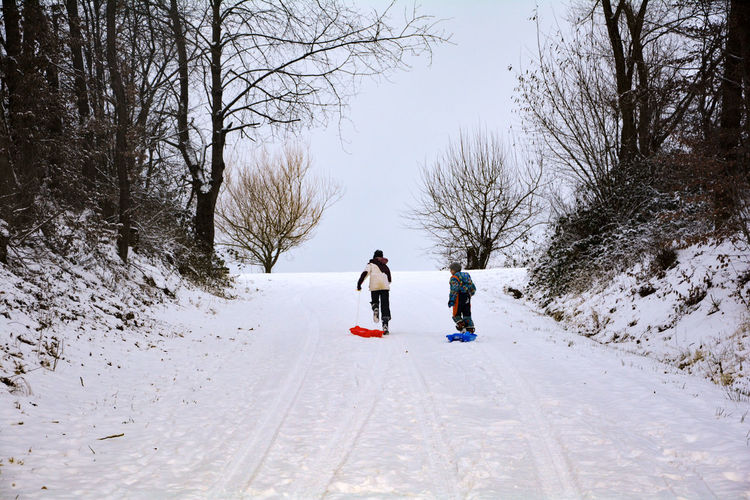 Boy and girl with sled running on snow covered land