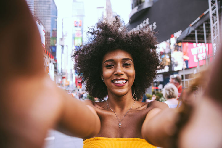 Portrait Of Happy Young Woman With Afro Hairstyle Taking Selfie On City Street