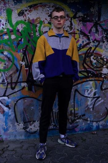 Portrait of teenage boy standing against graffiti wall