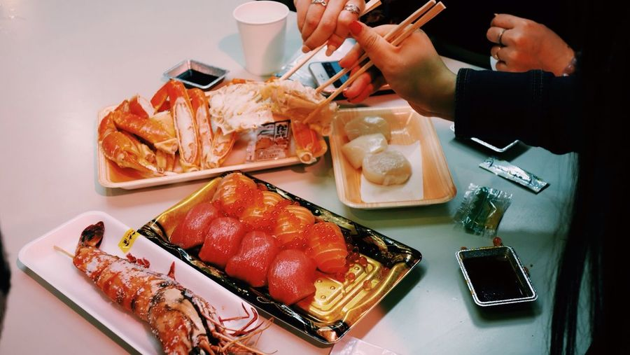 Cropped image of women having sushi at table in restaurant
