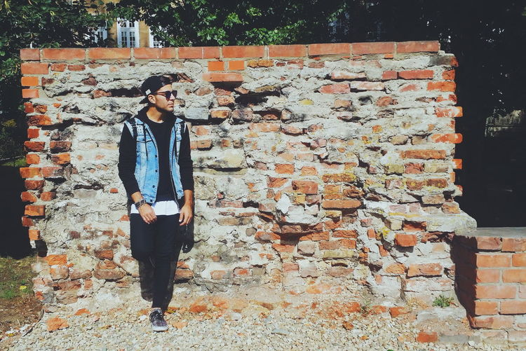 Full Length Of Man Leaning On Wall During Sunny Day