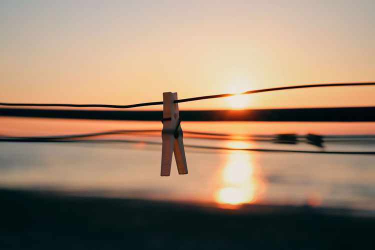 Close-Up Of Clothespins On Rope Against Sky During Sunset