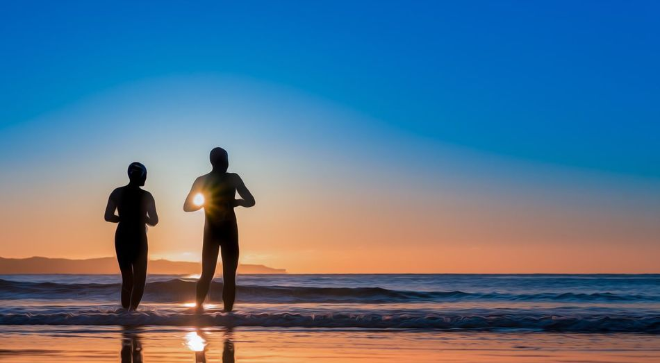 Rear view of silhouette couple standing at beach during sunset