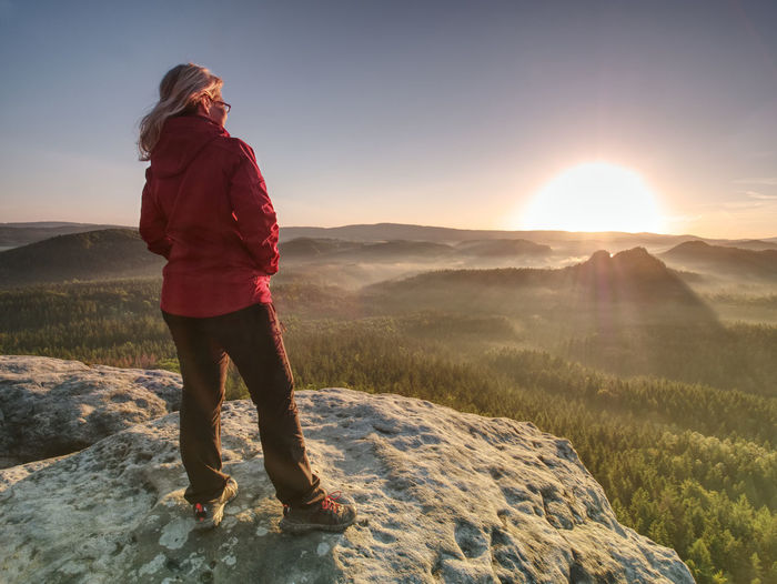 Blond hair girl tourist enjoy achievement of rocky summit with fantastic view into morning landscape