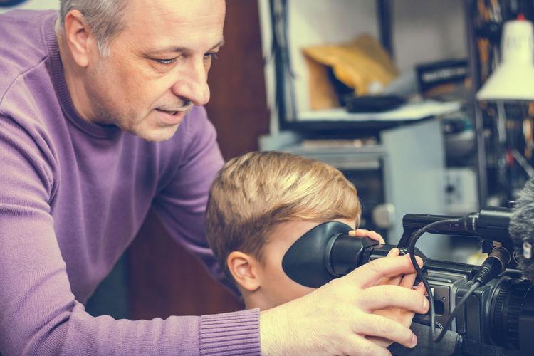 Grandfather teaching boy to use video camera