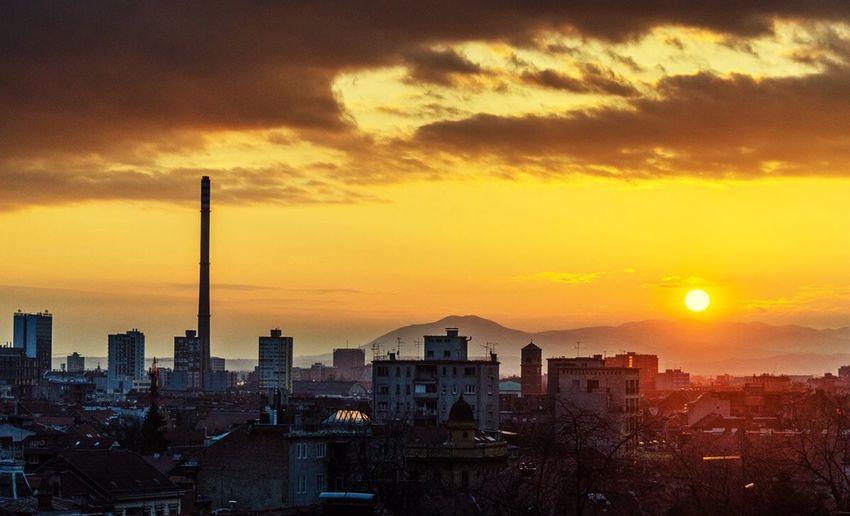 Cityscape against orange sky during sunset