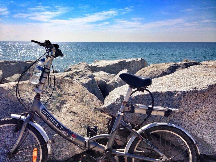 Bicycle on sea shore against sky during sunny day