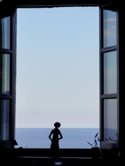 Silhouette man standing by window against clear sky