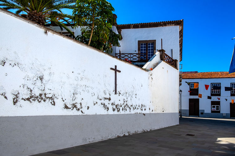 Church wall with cross - San Juan de la Rambla Old Town Street Village Tenerife Teneriffa Canary Islands SPAIN San Juan De La Rambla Travel Travel Destinations White City Home Wall Blue Sky Europe Ancient Tourism Windows Buildings Narrow Exterior Stone Architecture Built Structure Building Exterior Building Day No People Nature Residential District Wall - Building Feature Plant House Sky Clear Sky Tree Outdoors White Color Sunlight Roof
