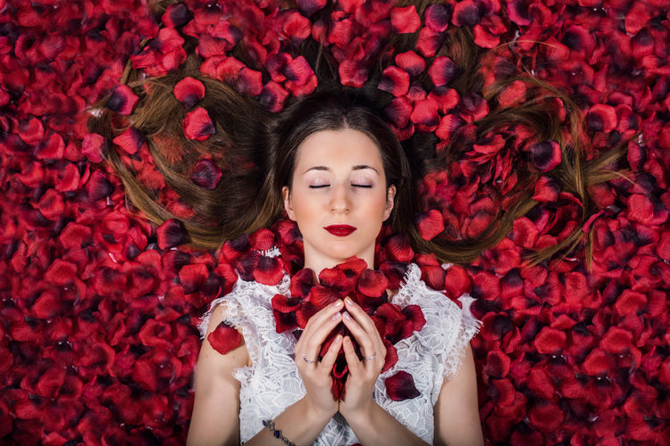 Directly above shot of woman lying on rose petals