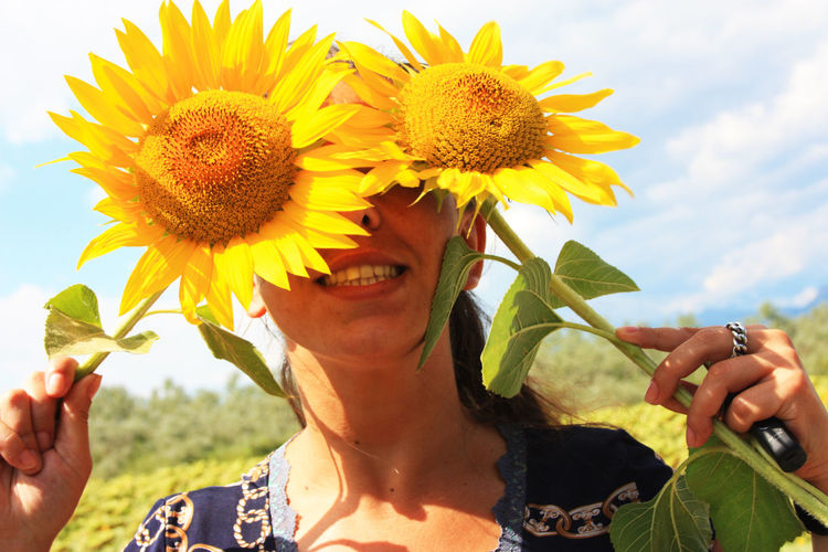 Caucasian brunette girl hides her eyes and part of her face behind two blooming yellow sunflower