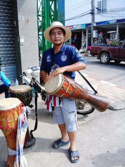 Portrait Of Man Carrying Drum While Standing In City