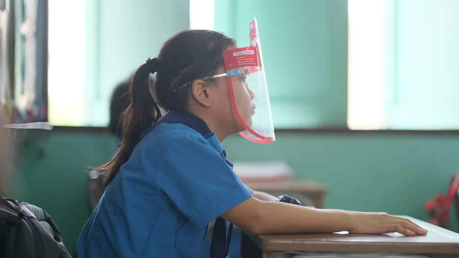 Side view of girl wearing face shied sitting at shield