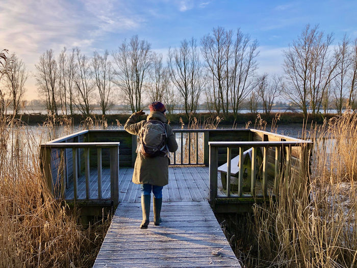 Rear view of woman standing by lake against sky during winter