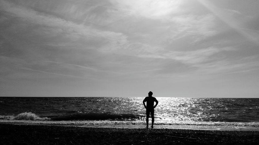 A contemplative man Man Contemplating Seascape Tuscany Under The Tuscan Sun Hot Spring Landscape Sunset Relax Blackandwhite Alone Love Mylove Bibbona  Water Sea Beach Wave Standing Silhouette Men Childhood Boys