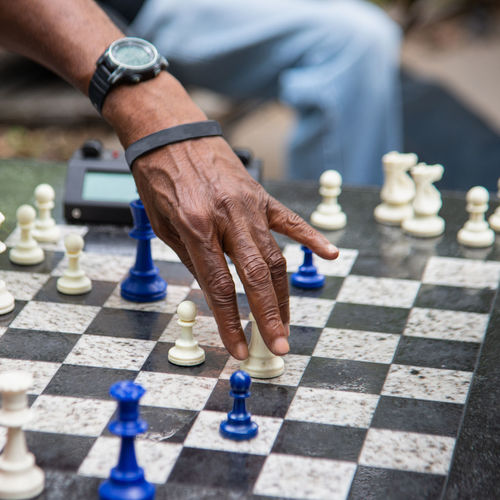 Midsection of man holding chess piece while playing chess outdoors