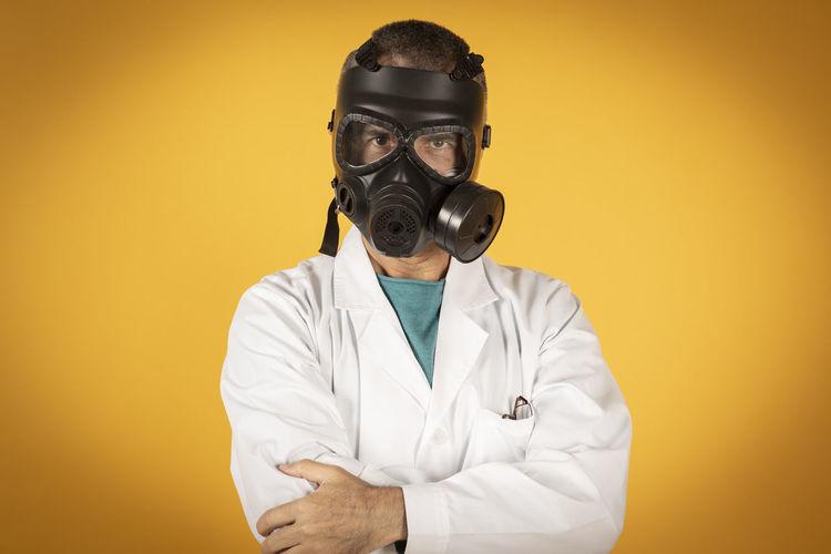 Portrait of man wearing gas mask against orange background